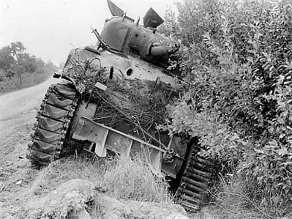 Sherman tank along a hedgerow in Normandy.
