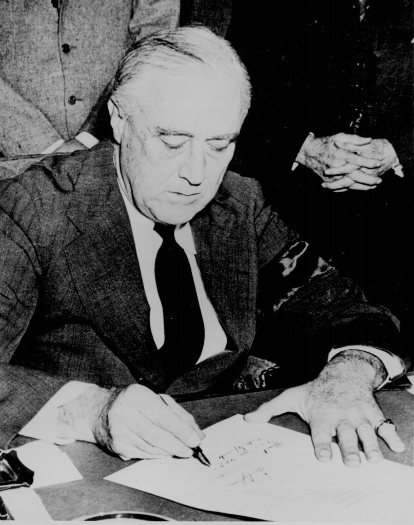 President Franklin D. Roosevelt signing the Declaration of War against Japan