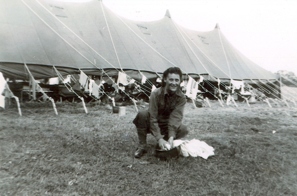 World War II Army nurse Jan Shimp doing laundry in a steel helmet in a Normandy cow pasture. Note the laundry hanging out to dry on the tent ropes.