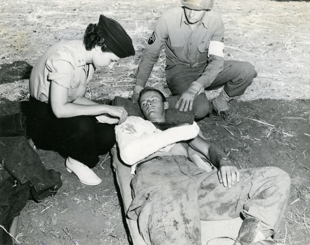 Army Nurse Verona Savinski, 802nd Medical Evacuation Transport Squadron, and Cpl. Claude W. Thomas of the 3rd Auxiliary Surgical Group, with Pfc. Joe Kirach of Brooklyn N.Y. 504th Parachute Infantry, who was strafed after rushing to the front after jumping D-Day.