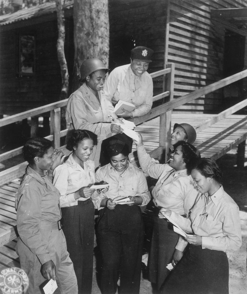 A group of African-American Army nurses stationed in the southwest Pacific area receive their first batch of home mail at their station. Three of the nurses are Lts. Prudence L. Burns, Inez Holmes, and Birdie E. Brown. 29 November 1943. Photo source: U.S. Army Signal Corps