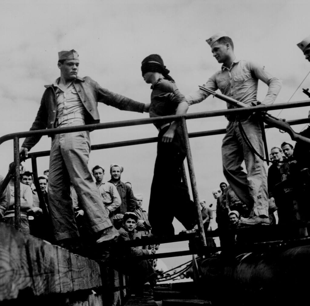 """Marines unloading Japanese POW from a submarine returned from war patrol."""" Lt. Comdr. Horace Bristol, ca. May 1945."""