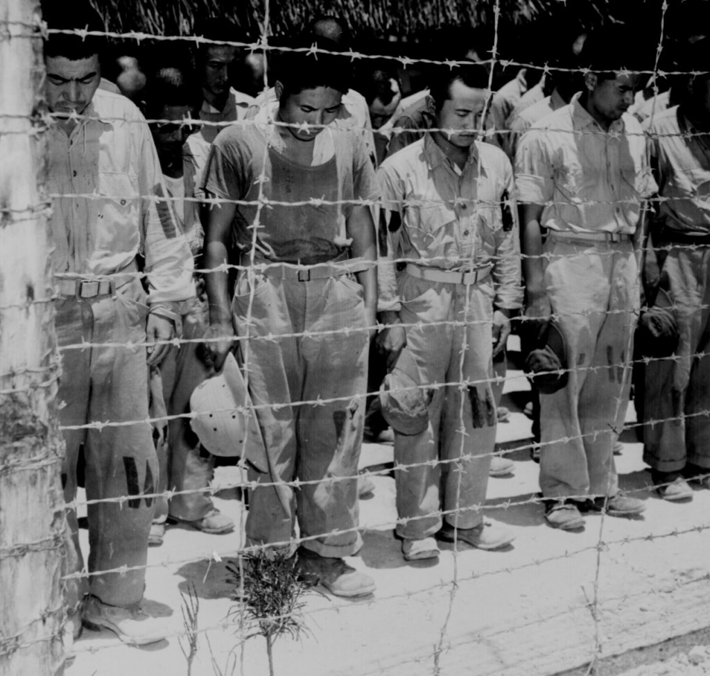 "Japanese POW's at Guam, with bowed heads after hearing Emperor Hirohito make announcement of Japan's unconditional surrender."" August 15, 1945."